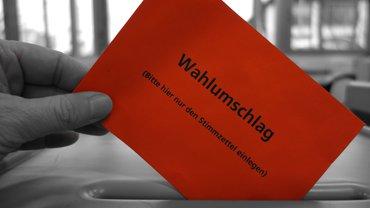 Roter Briefumschlag wird in eine Wahlurne eingeworfen